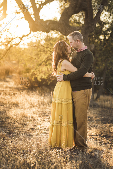 Woman embracing husband while in California field during sunset
