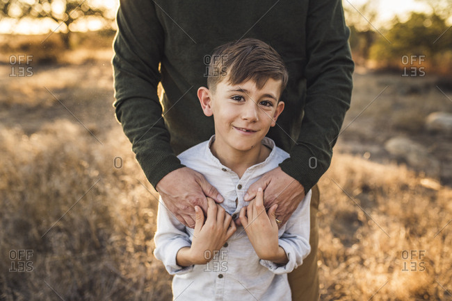 Close up of young boy being embraced by father in California field