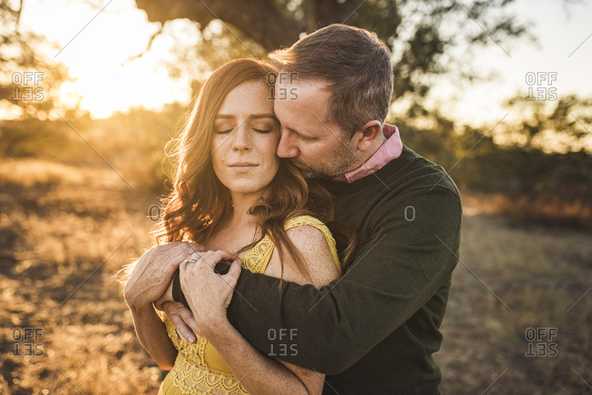 Husband embracing wife while in California field during sunset