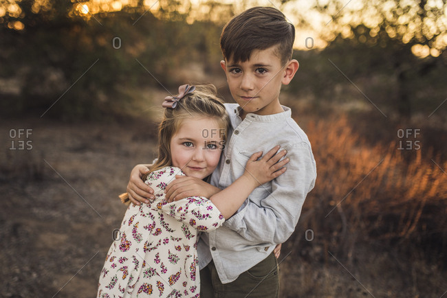 Young girl and boy hugging each other in California field at sunset