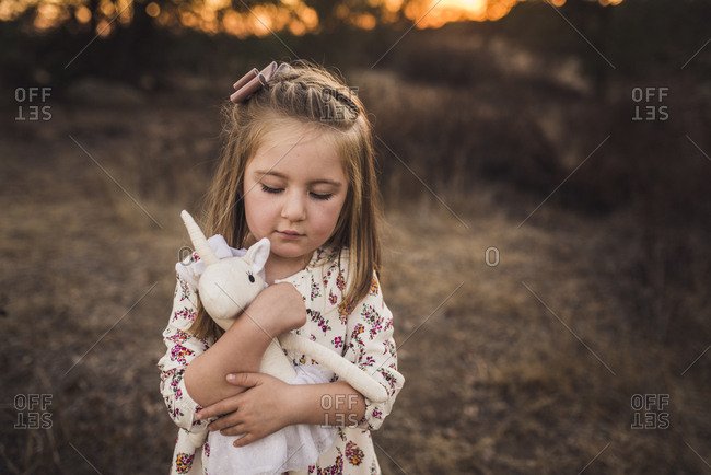 Portrait of young girl holding stuffed animal toy while looking down