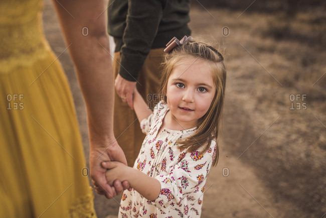 Young girl holding parents hand in California field at sunset