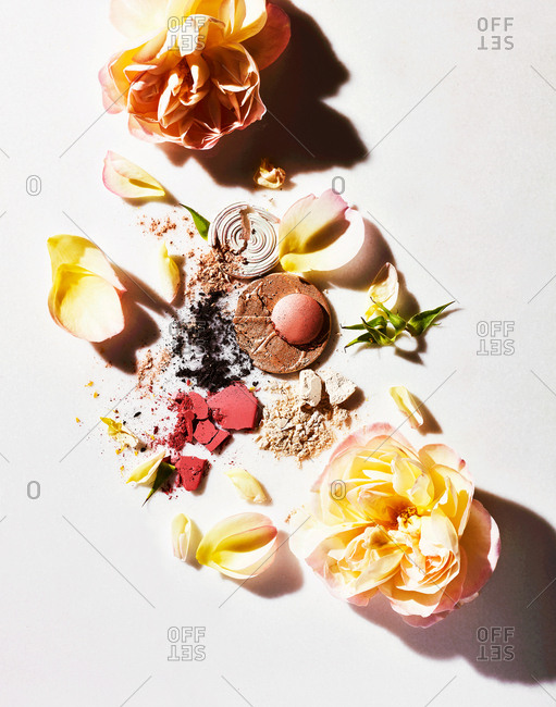 Powder cosmetics on white background with flowers