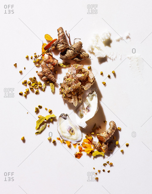 Oysters and turmeric root on white background