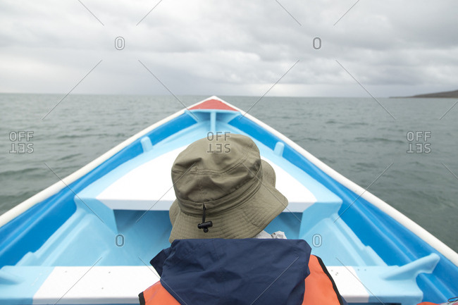 Person in a blue boat on a whale watching tour