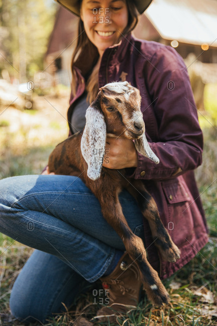 Smiling woman sitting down holding a baby goat.
