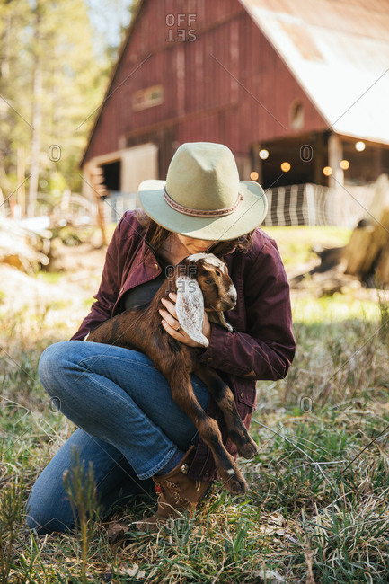 Woman cuddling a baby goat in front of a barn.