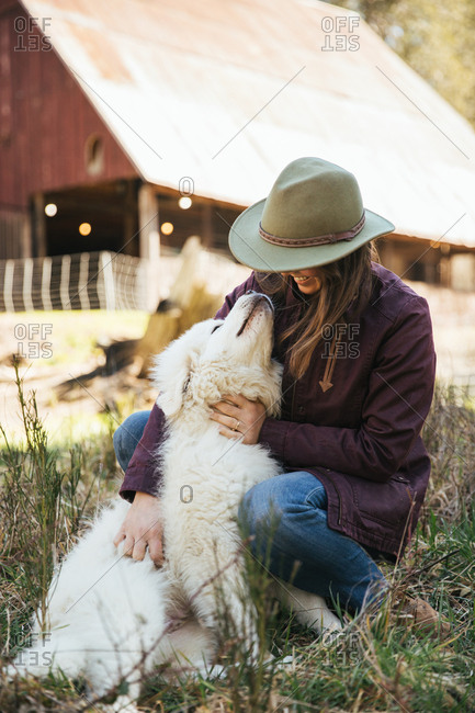 Woman petting a great pyrenees puppy in front of a barn.