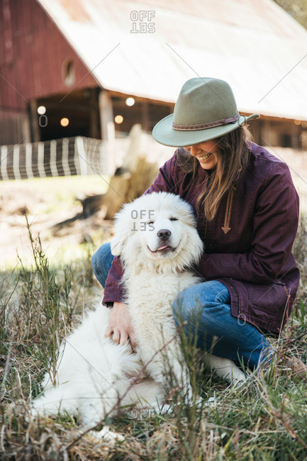 Woman petting a smiling great pyrenees puppy in front of a barn.