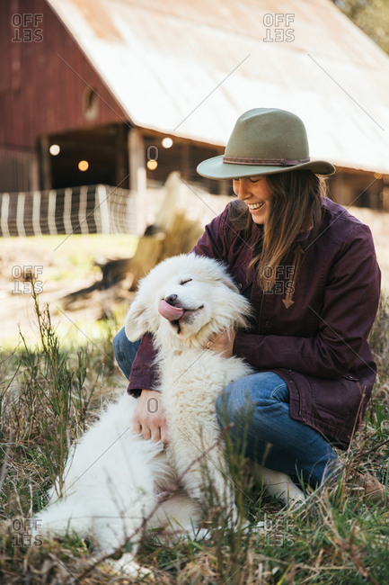 Woman cuddling a great pyrenees puppy in front of a barn while puppy licks lips.