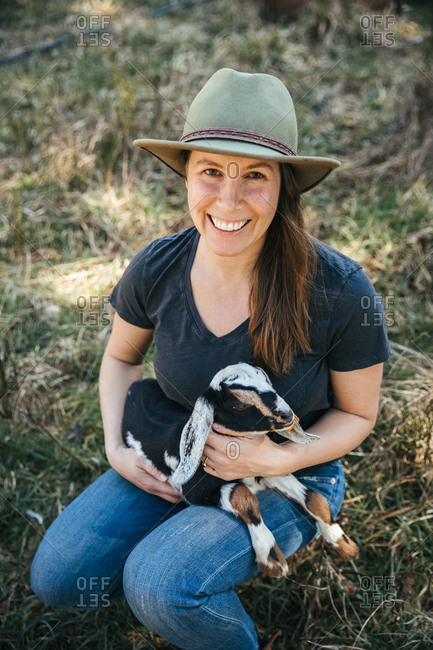 Woman in a hat holding a baby goat.