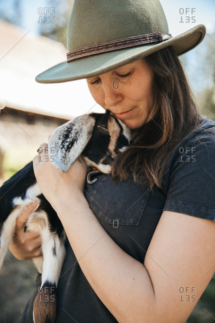 Woman in a hat holding a baby goat in front of  a barn.