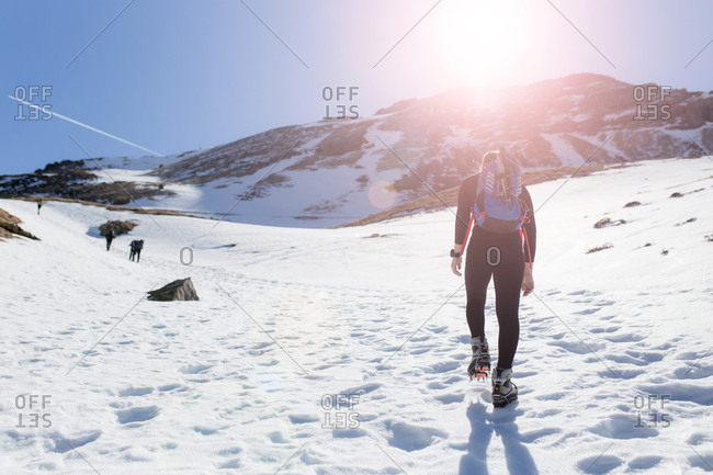 Rear view of young hiker woman climbing the top of the mountain with crampons by the snow in a sunny day