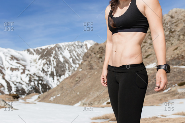 Detail of strong belly and abs of hiker woman in a sunny day mountains background