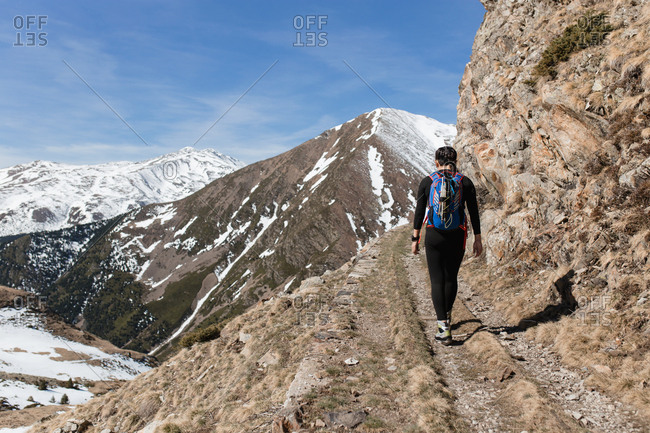 Rear view of hiker woman walking by a cliff in a sunny day mountains background