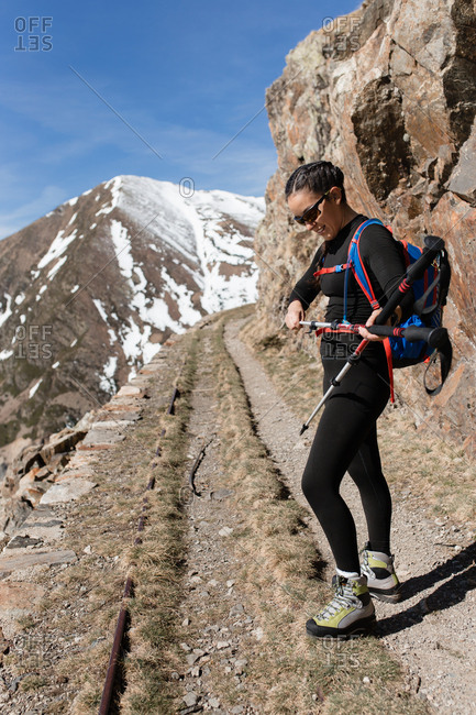 Side view of young hiker woman in a sunny day preparing her equipment mountains background