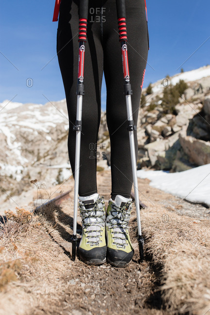 Detail of boots and trekking sticks walking by the mountain in a sunny day