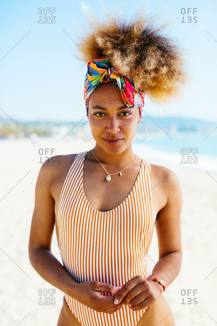 Portrait of a woman with afro hairstyle at beach looking at camera.