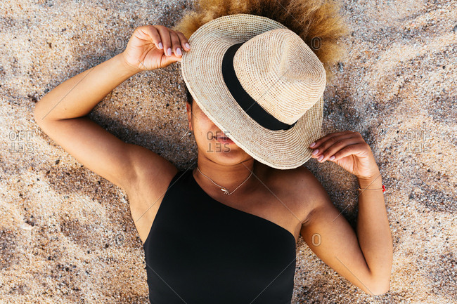 Woman resting on sand covering her face with sun hat.