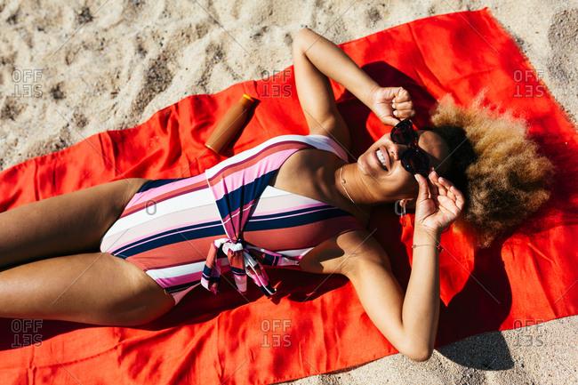 Woman with sunglasses sunbathing at beach.