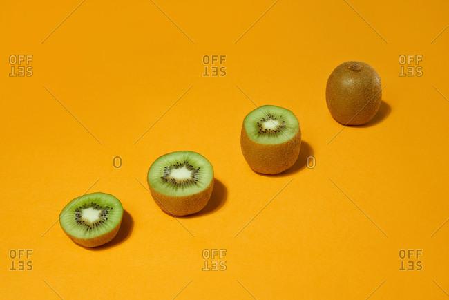 Fresh whole and cut kiwi  on yellow background. Development Concept.