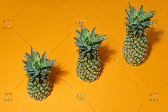 Fresh juicy pineapple stairs on yellow background. Development Concept.