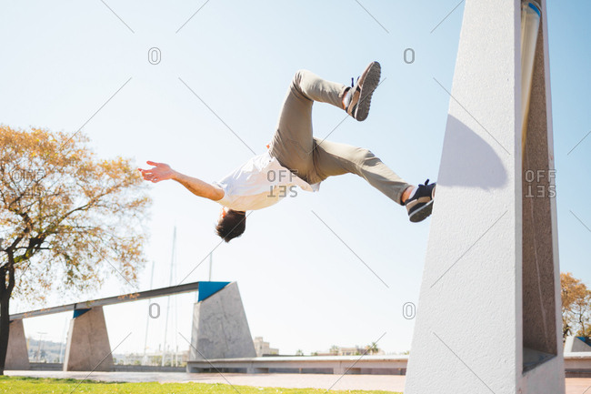 Young man performing a backflip in a green park