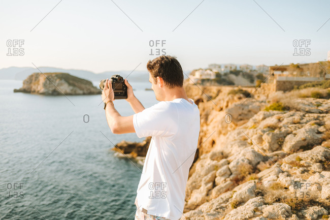 Young man taking picture of the amazing coastal view