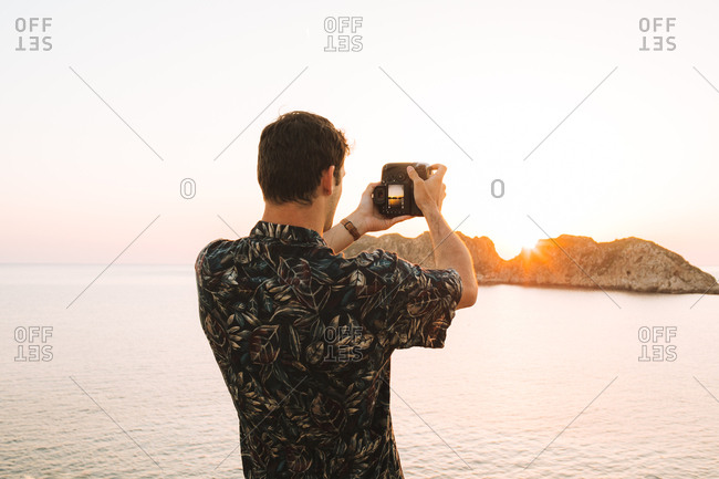 Man taking picture of sunset on the coast