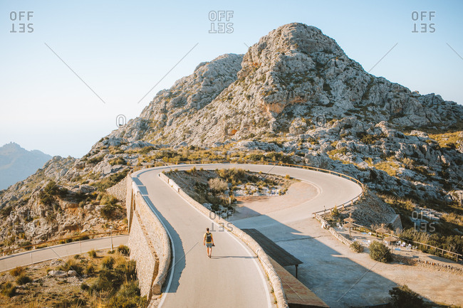 Amazing view of a curvy road, mountain and man walking