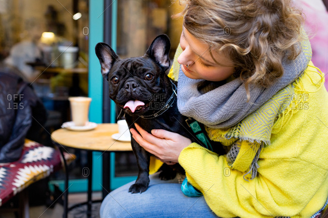 Young blonde woman holding black french bulldog on her knees at the outdoor cafe terrace