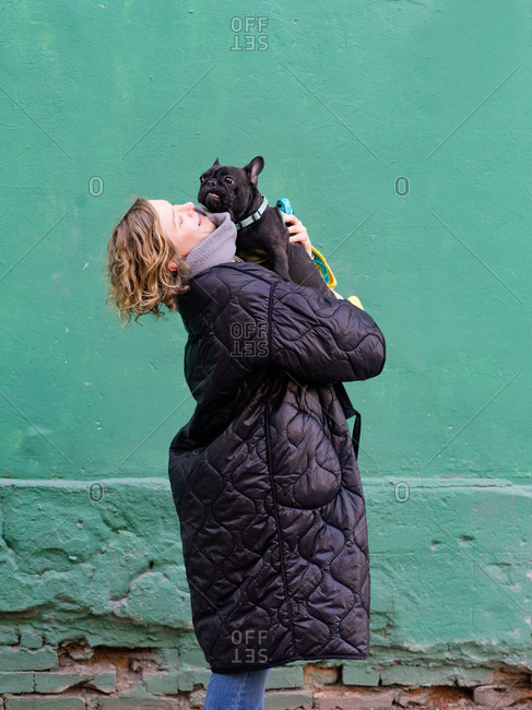 Young blonde woman holding black french bulldog in her arms