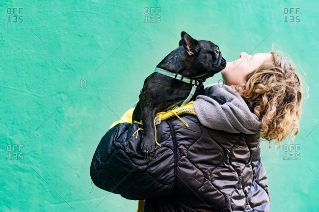 Girl playing with french bulldog