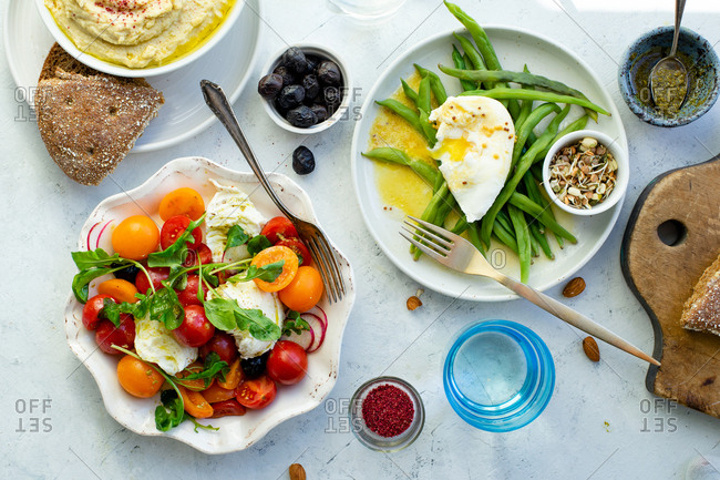 Overhead image of healthy lunch with mozarella tomato salad, green beans with poached egg and hummus