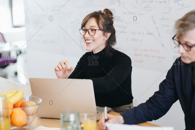 Candid portrait of beautiful female marketing expert working on new ideas within creative team during a meeting in office.