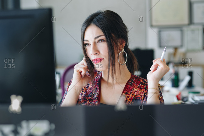 Attractive businesswoman talking on phone and looking at computer screen in office.