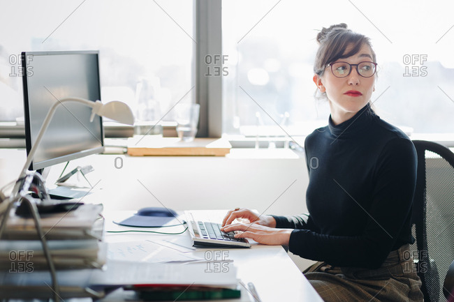 Candid portrait of business woman working and taking notes during a meeting in modern office space.