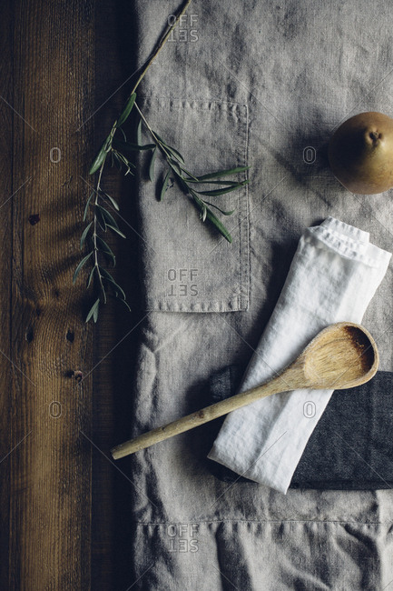 Pear and wooden spoon on an apron
