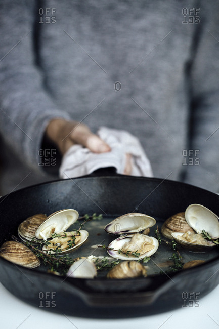 Person cooking clams in a skillet