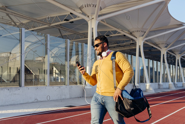 Attractive young bearded man with headphones and bag using phone and walking a track