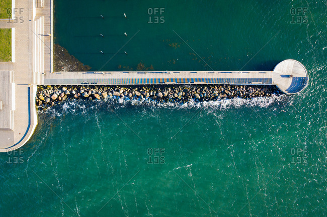 Overhead view of turquoise water surrounding pier