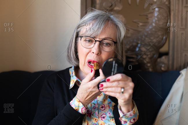 Senior woman applying pink lipstick