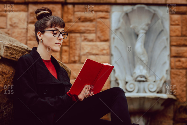 Side view of young attractive elegant woman in eyeglasses reading volume and sitting on stairs
