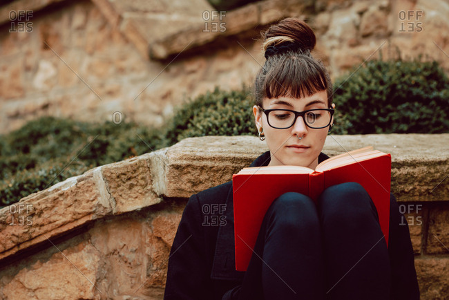 Young attractive elegant woman in eyeglasses reading volume and sitting on stairs