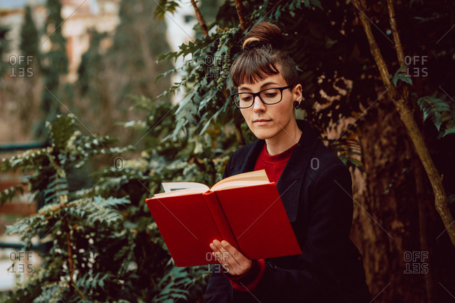 Young attractive elegant woman in eyeglasses reading volume and sitting on bench in city garden
