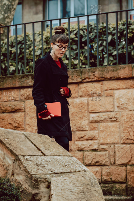Side view of young attractive elegant woman in eyeglasses holding volume and descending on stairs