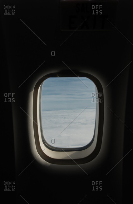 View of blue sky and thick clouds behind window of modern plane