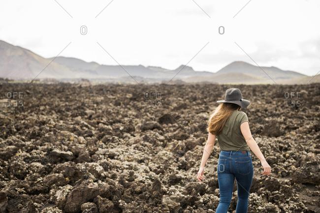 Woman walking against stony terrain