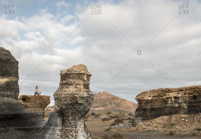Anonymous female sitting of stony terrain