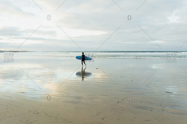 Side view of anonymous person in swimwear carrying blue surfboard while walking on wet sand near waving sea on cloudy day